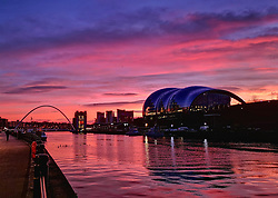 © Licensed to London News Pictures. 02/01/2020. Newcastle, UK. A bright sunrise on a winter morning over the River Tyne in Newcastle, north eats England, with the Sage music hall (right) and Millennium Bridge (left) pictured. Photo credit: Colin Scarr/LNP