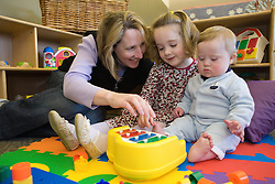 United States, Washington, Bellevue, woman and two children playing toy piano at Kindering Center