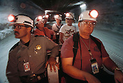 Safety tour at underground storage of radioactive wastes. This is one of the chambers of the Waste Isolation Pilot Project (WIPP), 700 meters below ground. WIPP is a research project to determine the suitability of the local salt rocks as a storage site for highly- radioactive transuranic waste from nuclear power stations. Such waste materials may have radioactive half-lives of thousands of years, and so must be isolated in a geologically stable environment. On the left is an experiment testing the design of containers carrying vitrified waste. The mine is located near Carlsbad, New Mexico, USA. (1998)