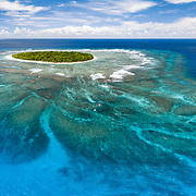 Aerial panorama of Fangasito Island in the Vava'u island group of the Kingdom of Tonga, with Fonua'one'one island visible in the background. From this perspective, the extent of the coral reef surrounding the island is visible.