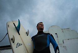 © Licensed to London News Pictures. 07/04/2014<br /> <br /> Saltburn, United Kingdom<br /> <br /> Surfer Richie Mitchell prepares to go for a surf as dark storm clouds form over Saltburn by the Sea in Cleveland.<br /> <br /> Photo credit : Ian Forsyth/LNP