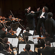 "December 12, 2012 - New York, NY : Conductor Gustavo Dudamel, standing at center, leads the  Westminster Symphonic Choir (not visible) and the Simón Bolívar Symphony Orchestra of Venezuela, along with tenor Idwer Álvarez, standing at right, and baritone Gaspar Colón, standing at left, as they perform Antonio Estévez's ""Cantata criolla"" at Carnegie Hall's Stern Auditorium / Perelman Stage on Tuesday evening.  CREDIT: Karsten Moran for The New York Times"