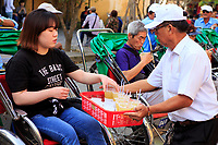 A man gives a tourist a cool drink before a rickshaw ride through the old town of Hoi An