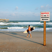 A surfer makes his way into the waves at Wrightsville Beach, NC...