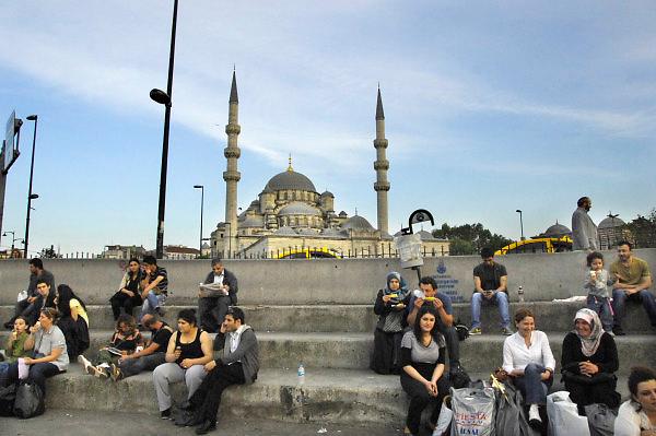 Turkije, Istanbul, 4-6-2011Straatbeeld. Aan de voet van de Galatabrug. Op de achterond de Nieuwe Moskee. Vrouwen en mannen zitten op een rustplek met elkaar te praten.Foto: Flip Franssen