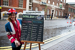 © London News Pictures. 25/04/2015. A Paddy Power bookmakers employee poses next to Paddy Power betting  odds on the name of the royal baby, outside the entrance to Lindo Wing of St Mary's hospital in Paddington. London, where The Duchess of Cambridge is due to give birth. Photo credit: Ben Cawthra/LNP
