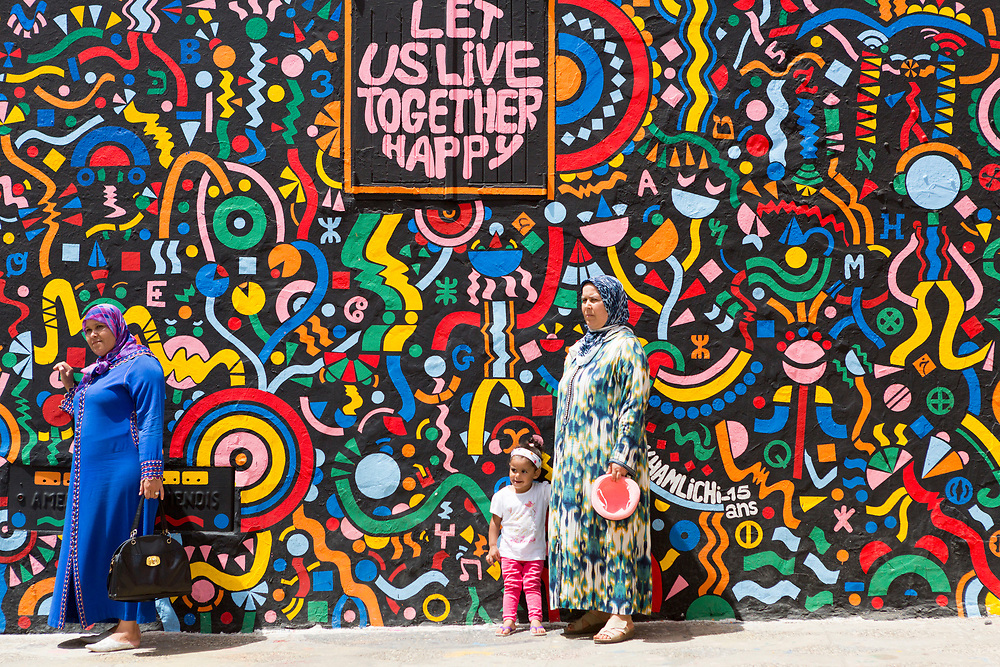 Tourists visit and take photos next to street art murals painted on the walls and architecture inside the seaside town during the International Cultural Festival, Asilah, Northern Morocco, 2015-08-11.<br /><br />Asilah is a sleepy fishing town in the North of Morocco, just one hour south of Tangier. While not completely off Morocco's well-beaten path, it's often missed by travellers bound inland for Fez or Chefchaouen, yet has a uniquely alluring charm. With an immaculately restored medina that's re-painted vivid shades of blue & white each summer, Asilah has the feel of being Morocco's own Santorini - a great spot to see the more chilled out, seaside town life in Morocco.  <br /><br />Asilah is synonymous with art and the peaceful seaside town is home to over 50 resident artists. It is packed full of art galleries, studios and exhibition spaces with artists from around the country selling their work. Each summer, the town invites artists from across the globe to visit and take part in an annual arts festival. The festival begins in July and commences by the artists and locals re-painting the medina. They purposefully leave large spaces of the medina walls white-washed blank, ready for artists to create and design new murals and street art during the festival. Artwork can be found everywhere, including sketches and engravings etched onto doorways and walls by children. Large sections are even allocated for children to paint their own ideas and fun workshops are held encouraging children to work together and help paint new murals onto the walls. This is actually how Asilah began its synonymous relationship with art. In 1978 seven Moroccan artists were invited to the town to hold art classes for children, inviting them to draw on the walls of the medina. The festival goes on for a number of weeks showcasing a range of artistic disciplines, from music and poetry to performance and painting, and everything inbetween. Its mark is left on the town for the remainder of the