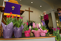 Sandra Stafford and Judy Robertson decorate Gilford Community Church with Lilies, Tuplips and Hyacynths for their Easter Sunday services.  (Karen Bobotas/for the Laconia Daily Sun)