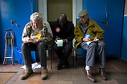 Three tellers from the main political parties check the addresses of voters in Herne Hill Methodist Church SE21 that serves as a temporary Polling station for voters on Britain's general election day. Their job is to record the election numbers of those about to vote, making sure that their political colleagues don't drop more literature in to that address, now that the occupants have voted.