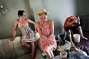 Two friends of Calin, one of the squatters living in the Wildwood Road mansion, Karina, 28, from Poland, (left) and Meshell, 36, from England, (centre) are laughing in the living room during a warm summer afternoon, while Pete, 23, from Lincolnshire, (right) is shaving his head, on Sunday, Aug. 5, 2007, in Hampstead, London, England. Situated opposite Hampstead Heath, North London's green jewel the average price for properties on this road reaches £ 2,500,000. Million Dollar Squatters is a documentary project in the lives of a peculiar group of squatters residing in three multi-million mansions in one of the classiest residential neighbourhoods of London, Hampstead Garden. The squatters' enthusiasm, their constant efforts to look after what has become their home, their ingenuity and adventurous spirit have all inspired me throughout the days and nights spent at their side. Between the fantasy world of exclusive Britain and the reality of squatting in London, I have been a witness to their unique story. While more than 100.000 properties in London still lay empty to this day, squatting provides a valid, and lawful alternative to paying Europe's most expensive rent prices, as well as offering the challenge of an adventurous lifestyle in the capital.