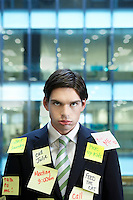 Businessman covered with Post-It notes