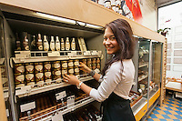 Portrait of smiling saleswoman arranding products in supermarket