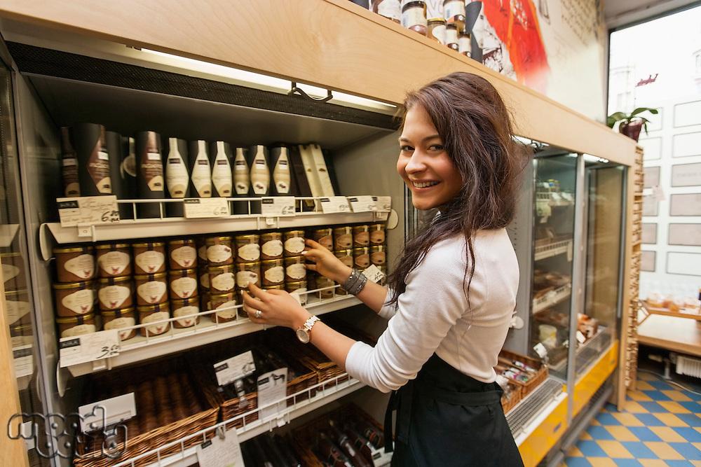 Portrait of smiling saleswoman arranding products in supermarket