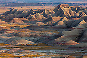 Soft light shows up the subtly colored rocks of the Badlands National Park in South Dakota, USA. Most of the visible geological features at higher elevations are from the Sharps and Brule Formations, which are the youngest rocks and contain a high content of wind-blown ash from earlier volcanic activity to the west.