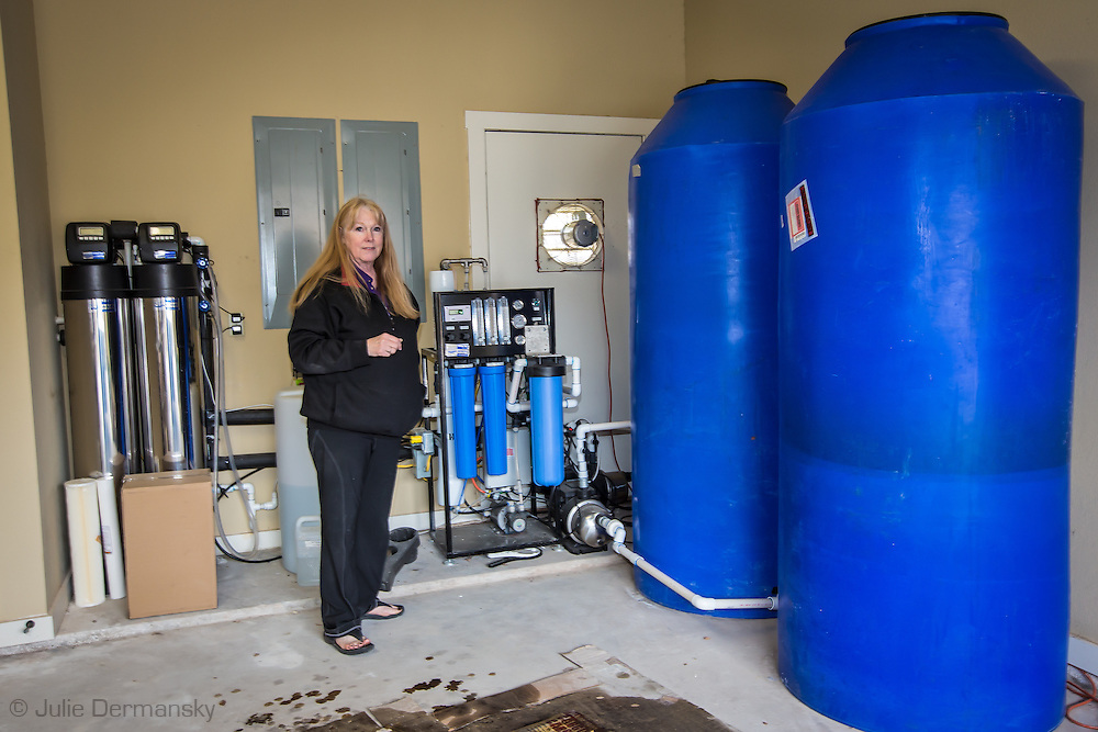 Elizabeth Falconer with a water cleaning unit she bought after the fracking industry contaminated the water in Weatherford, Texas. She doesn't drink the 'cleaned water, but uses it to shower and clean. She buys drinking water.