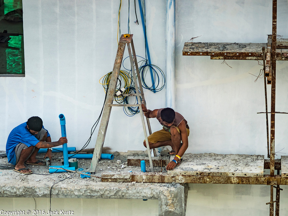 "23 AUGUST 2016 - NONTHABURI, NONTHABURI, THAILAND: Construction workers work on buildings near the ""Purple Line,"" the new Bangkok commuter rail line that runs from Bang Sue, in Bangkok, to Nonthaburi, a large Bangkok suburb. The Purple Line is run by the  Metropolitan Rapid Transit (MRT) which operates Bangkok's subway system. The Purple Line is the fifth light rail mass transit line in Bangkok and is 23 kilometers long. The Purple Line opened on August 6 and so far ridership is below expectations. Only about 20,000 people a day are using the line; officials had estimated as many 70,000 people per day would use the line. The Purple Line was supposed to connect to the MRT's Blue Line, which goes into central Bangkok, but the line was opened before the connection was completed so commuters have to take a shuttle bus or taxi to the Blue Line station. The Thai government has ordered transit officials to come up with plans to increase ridership. Officials are looking at lowering fares and / or improving the connections between the two light rail lines.     PHOTO BY JACK KURTZ"