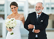 The bride walks down the aisle escorted by her father at the Wychmere Beach Club in Harwichport