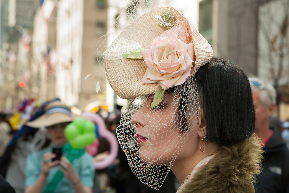 A woman in a hat and veil reminiscent of the 1940s.