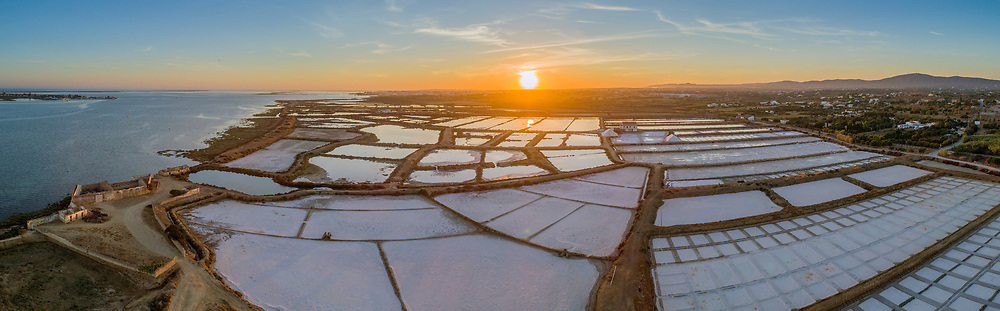 Sunset aerial panoramic view, in Ria Formosa wetlands natural park, salt production pans in the foreground, Algarve. Portugal.