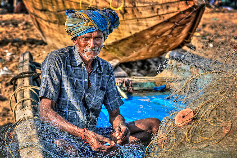 old fisherman is reparing a fishingnet