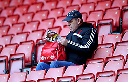 A fan in the stands reads through a match programme prior to the Premier League match at St Mary's Stadium, Southampton.
