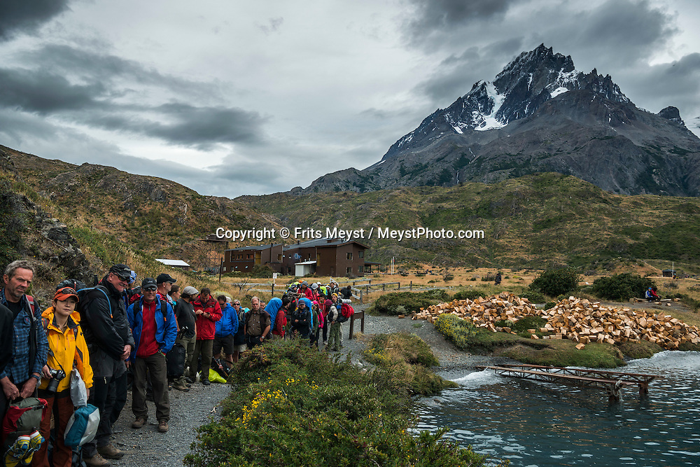 Patagonia, Chile, February 2016.  Hikers waiting for the Catamaran ferry on the 'W' on their way to the Grey Glacier Lookout. The most highly trekked route in Torres del Paine National Park is called the 'W'. This trail system can be done in a variety of ways, from more rugged camping style treks, to full room and board in refugios. The W Circuit is named after its trail system that navigates up and down out of the mountain valleys. Torres del Paine is a UNESCO World Biosphere Reserve and encompasses mountains, glaciers, lakes, and rivers in southern Chilean Patagonia. The Cordillera del Paine is the centerpiece of the park. It lies in a transition area between the Magellanic subpolar forests and the Patagonian Steppes. A 4x4 camper is one of the best vehicles to explore the wild interior of Southern Patagonia. Photo by Frits Meyst / MeystPhoto.com