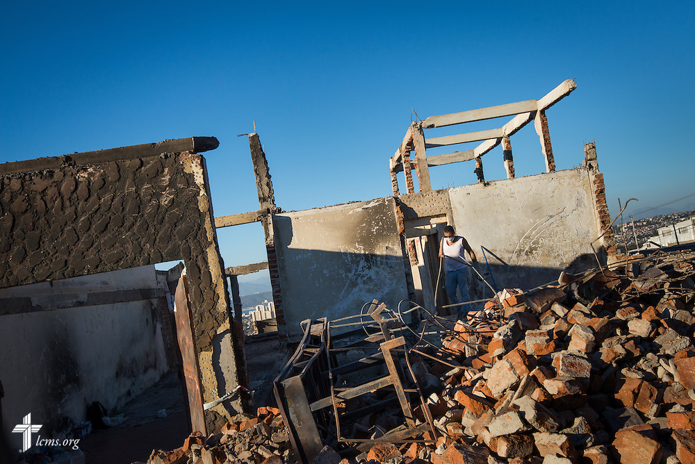 A man walks through debris Monday, April 21, 2014, on a hillside of homes affected by a devastating fire in Valparaíso, Chile. The catastrophic fire that tore through the hillsides above the historic port city fire killed 15 people, destroyed about 3000 homes, and left approximately 15,000 people homeless.  LCMS Communications/Erik M. Lunsford
