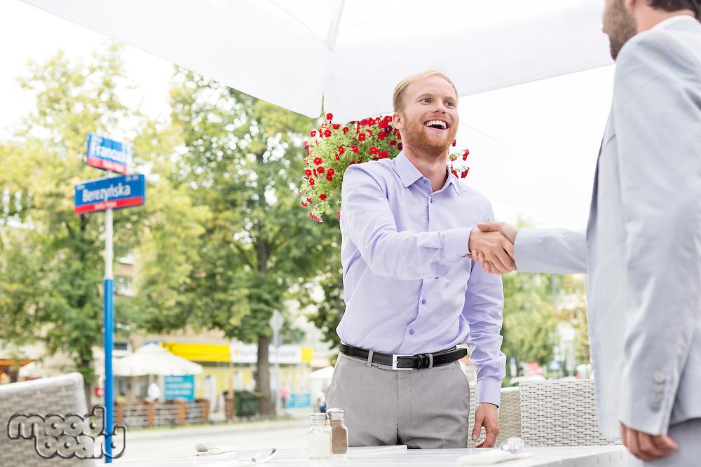 Happy businessmen shaking hands at outdoor restaurant