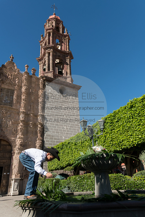 A young Mexican boy decorates a fountain outside the San Francisco Church in preparations for celebrating El Viernes de Dolores during Holy Week March 23, 2018 in San Miguel de Allende, Mexico. The event honors the sorrow of the Virgin Mary for the death of her son and is an annual tradition in central Mexico.