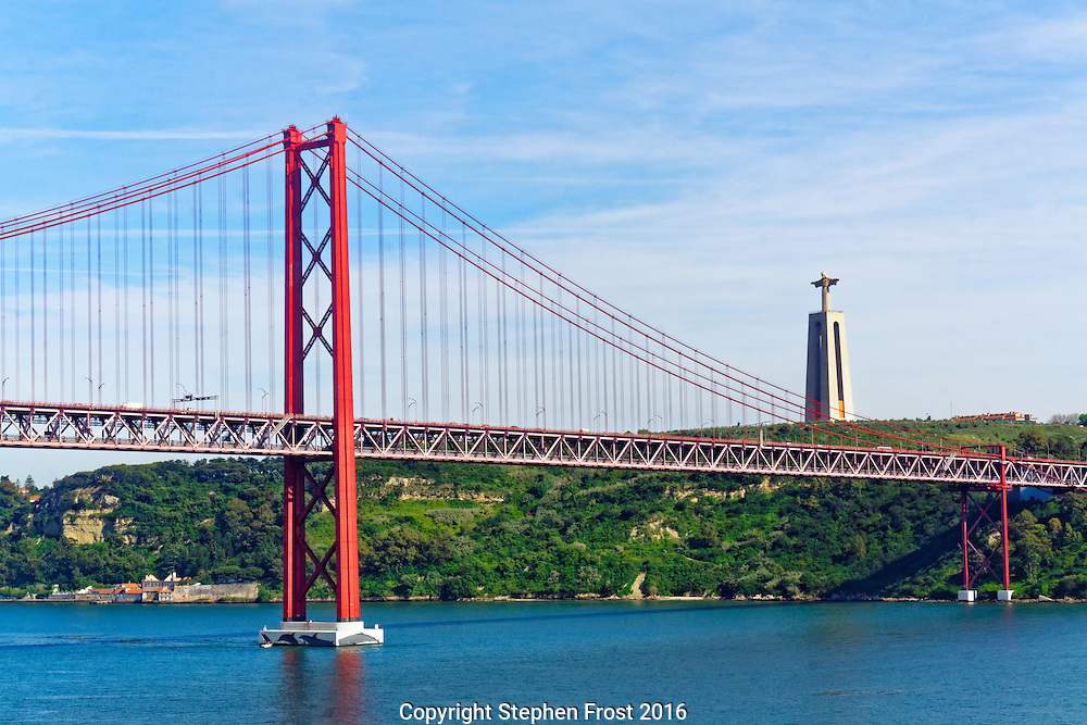 The 25th April Bridge, connecting Lisbon, Portugal, with Almada, across the Tejo river. The statue on the far bank is entitled Christ the King.