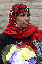 © Licensed to London News Pictures. 15/07/2016. Batley, UK. A woman holds flowers as she waits for Jo Cox's funeral cortege to pass through her hometown of Batley, West Yorkshire. The Labour MP was stabbed and shot in the street as she left her constituency surgery last month. Thomas Mair was arrested in connection with the murder and is set to face trial this year.  Photo credit : Ian Hinchliffe/LNP