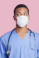 Mixed race male surgeon wearing surgical mask over pink background