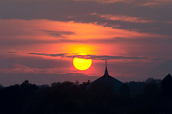 © Licensed to London News Pictures. 14/04/2019.<br /> Orpington, UK.The sun setting this evening behind St Barnabas church spire in St Pauls Cray, Orpington, South East London.  Photo credit: Grant Falvey/LNP