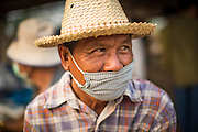 06 APRIL 2013 - SANPATONG, CHIANG MAI, THAILAND: A farmer with a face mask in the market in the market in Sanpatong, Chiang Mai province, Thailand. The buffalo market in Sanpatong (also spelled San Patong) started as a weekly gathering of farmers and traders buying and selling water buffalo, the iconic beast of burden in Southeast Asia, more than 60 years ago and has grown into one of the largest weekend markets in northern Thailand. Buffalo and cattle are still a main focus of the market, but traders also buy and sell fighting cocks, food, clothes, home brew and patent medicines.       PHOTO BY JACK KURTZ