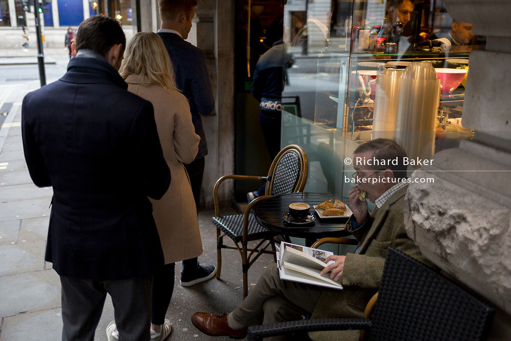 While sitting on a seat outside a sandwich bar on Air Street, off Piccadilly, a queue of customers queue for their lunches, as another customer takes a bite into his sandwich, on 5th November 2019, in London, England.