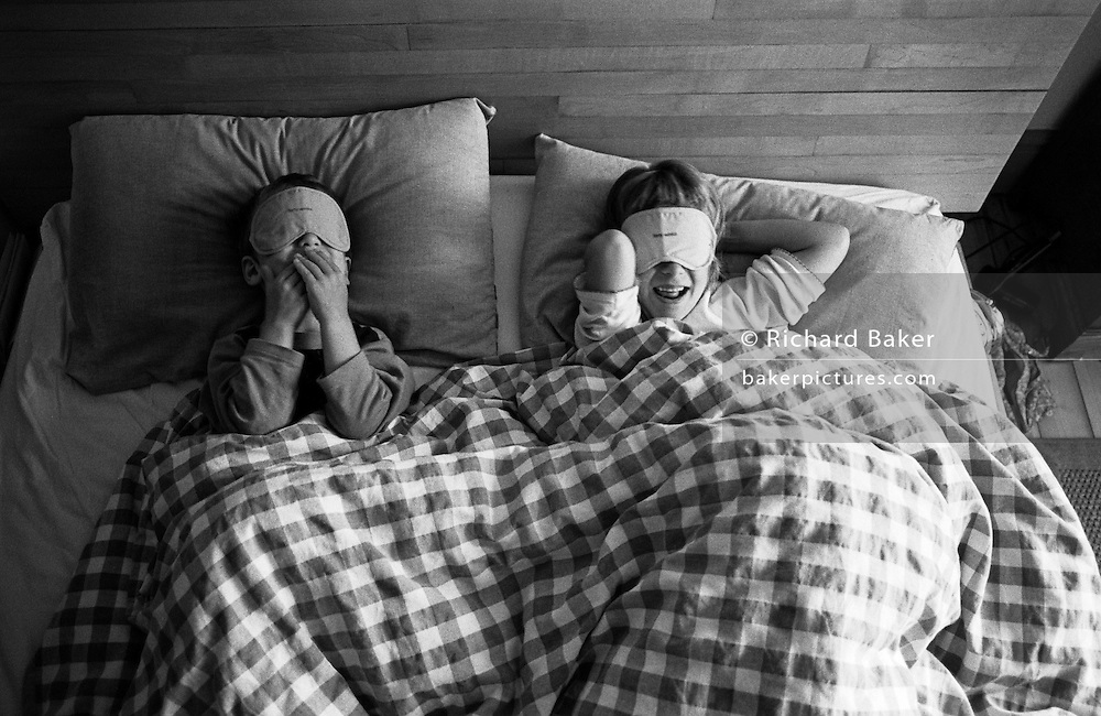 "Looking down on them from above, we see a brother and sister play with free airline blindfolds while in their parents' bed at the family home in South London. Pretending to be blind, they giggle at this hilarious and childish game as if acting out the speak and see no evil. From a personal documentary project entitled ""Next of Kin"" about the photographer's two children's early years spent in parallel universes. Model released."