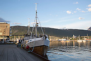 Arctic cathedral church and Tromso Bridge, city of Tromso, Norway, from harbour quayside with fishing trawler