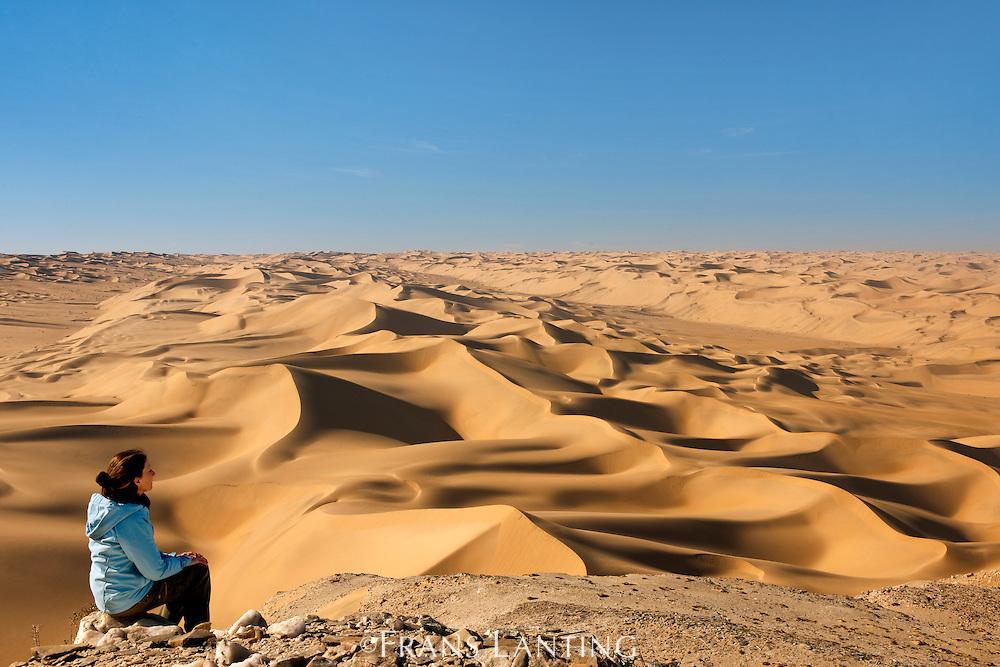 Hiker watching sand dunes, Saddle Hill, Sperrgebiet National Park, Namibia, Model release