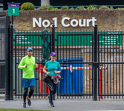 © Licensed to London News Pictures. 31/03/2020. London, UK. A couple run past the The All England Lawn Tennis Club, Wimbledon. AELTC is set to announce on Wednesday (1 April) the cancellation of the Wimbledon Tennis Championships 2020 due to the coronavirus pandemic. The pandemic has led to the cancellation of major sporting events across the World as the coronavirus crisis continues. Photo credit: Alex Lentati/LNP