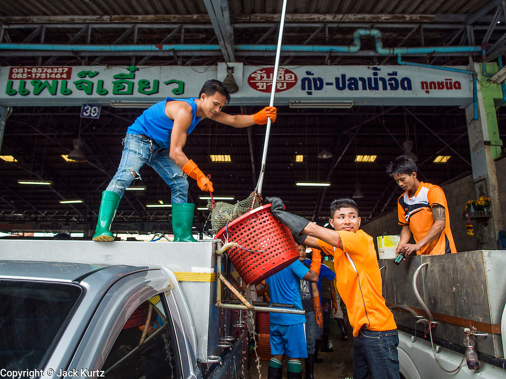 20 JUNE 2014 - SAMUT SAKHON, SAMUT SAKHON, THAILAND: Burmese migrant workers unload a truckload of farm raised shrimp at a processing center in Samut Sakhon. Hundreds of thousands of migrant workers from Myanmar work in the Thai fishing industry. Samut Sakhon, (sometimes still called Mahachai, its historical name) is a large fishing port. Many Burmese live in the town and work in the fish process plants. Although hundreds of thousands of Cambodians fled Thailand last week after the military coup, the Burmese workers have stayed and are still working in many Thai towns.    PHOTO BY JACK KURTZ