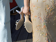 A woman holding her high heeled shoes in her hand