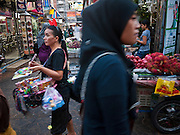 06 JULY 2011 - BANGKOK, THAILAND: A Muslim woman walks past a souvenir vendor on Soi Arab in Bangkok. Soi Arab is an alleyway in Bangkok. What started as an alley has now grown into a neighborhood that encompasses several blocks of restaurants, hotels and money exchanges that cater to Middle Eastern visitors to Thailand. The official name of the street is Sukhumvit Soi 3/1, located in North Nana between Sukhumvit Soi 3 and Sukhumvit Soi 5, not far from the Nana Plaza night-life area and the Grace Hotel popular among Arabs.   PHOTO BY JACK KURTZ