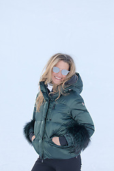 woman in winter coat and sunglasses outdoors