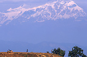 Seen from a hillside opposite, with the clear blue backdrop of the snow-covered Himalayan mountain peaks, a Nepalese family crouch on the hilltop to rest during a family walk from their community village near Gorkha, Central Nepal. In the middle of the picture, a young girl twirls and dances across the clearing as her parents and siblings watch, drawfed by the powerfully- dominant range of natural features that form part of the highest altitudes on earth although Gorkha is only 3281 feet (about 1000 meters) above sea level. These peoples' homes cling to the sides of impressive mountains that draw tens of thousands of travellers to this region to trek the paths and conservation sanctuaries of this fast-developing Buddhist and Hindu Kingdom.