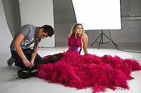 Fashion stylists adjusts model's footwear in studio