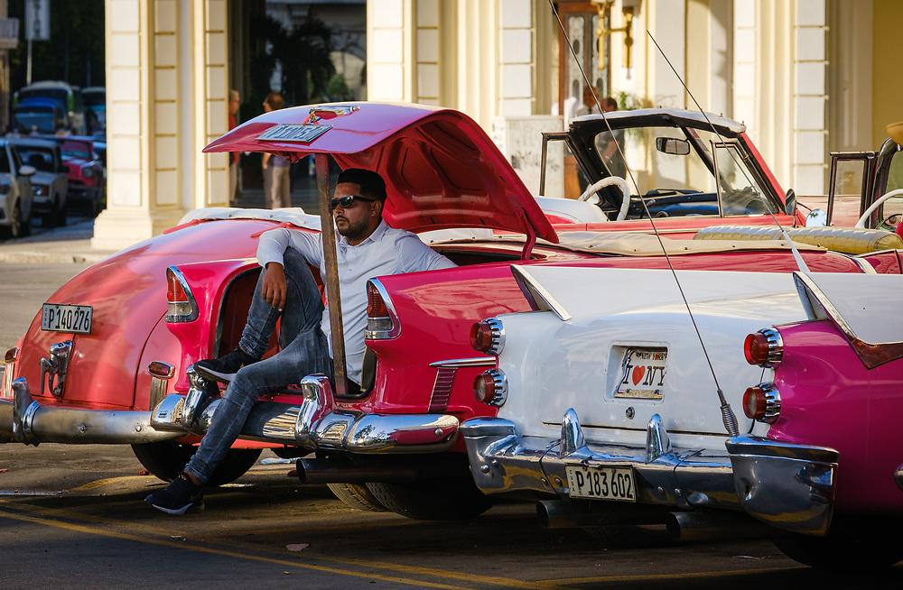 HAVANA, CUBA - CIRCA JANUARY 2020: Driver and old  classic cars in Havana.