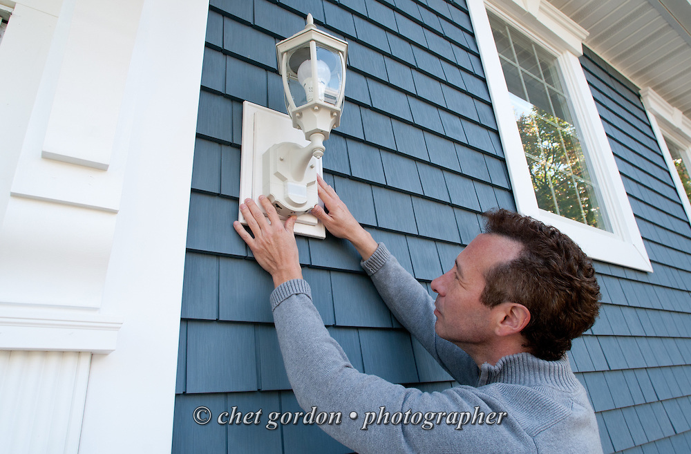 Craig Furer inspects an electrical lamp mounted near the front door of his Cranford, NJ home on Sunday, October 23, 2016. Furer and his wife Jen hired Magnolia Home Remodeling Group to complete a full exterior makeover. The company replaced the siding with shake and clapboard, added various architectural accents, replaced the roof, modified the roofline, built a front portico and replaced two windows. Craig spent a lot of time researching this project before it began and is thrilled with the overall result.  © Chet Gordon for Angie's List