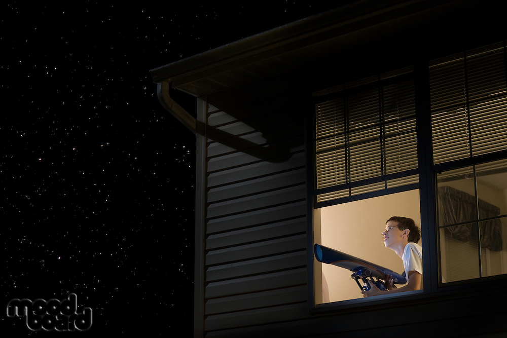 Teenage boy stands with telescope at open window looking at night sky