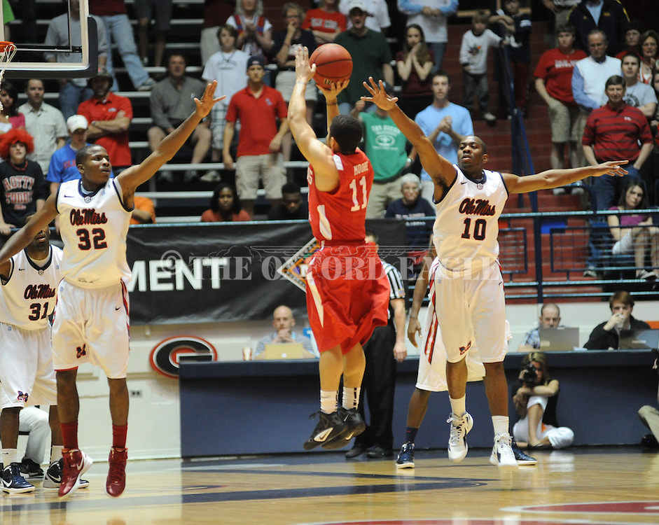 "Illinois State's Nic Moore (11) makes a three pointer over Ole Miss' Jarvis Summers (32) and Ole Miss' LaDarius White (10) in a National Invitational Tournament game at the C.M. ""Tad"" Smith Coliseum in Oxford, Miss. on Wednesday, March 14, 2012. Illinois State won 96-93 in overtime. (AP Photo/Oxford Eagle, Bruce Newman)"