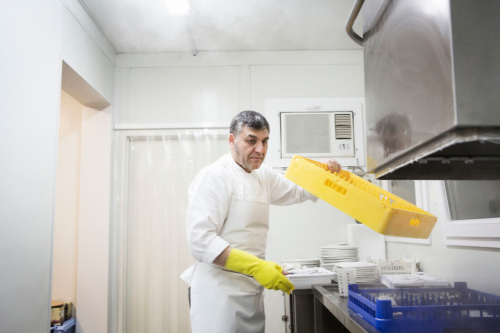 """MILANO, ITALY - 1 MARCH 2016: Aggi Bislimaj, an inmate from Kosovo, works as a dishwasher at the """"InGalera"""" restaurant in the Bollate prison in Milan, Italy, on March 1st 2016.<br /> <br /> """"InGalera"""" (which translates in English as """"InJail"""") is the first restaurant located inside a prison and offering high-quality cooking to the public and a future to the inmates. It was inaugurated last October inside the Bollate prison in Milan. It is open five days a week for lunch and dinner, and seats 55 people. There are 9 people involved in the project, including cooks and waiters, all regularly employed and all inmates of the prison, apart from the chef and the maître d'hôtel, recruited from outside to guarantee the high quality of the food served. The restaurant is a project of the co-operative ABC La Sapienza - that operates inside the prison and provides more than 1,000 meals three times a day with the help of inmates they've hired - and of PwC, a multinational operating in the field of corporate consultancy. The goal of this project is to follow prisoners in rehabilitation process of social inclusion.<br /> <br /> The Bollate prison is already known for being a good example of penitentiary administration. The inmates are free to move around from one area to the other inside the prison (their cells open at 7:30am and close at 9pm) to go study, exercise in a gym, or work (in a call center, as scenographers, tailors, gardeners, cooks, typographers, among others)  in one of the 11 co-operatives inside the prison or in one of the private partnering businesses outside the prison. The turnover of the co-operatives that work inside the prison was €2mln in 2012."""